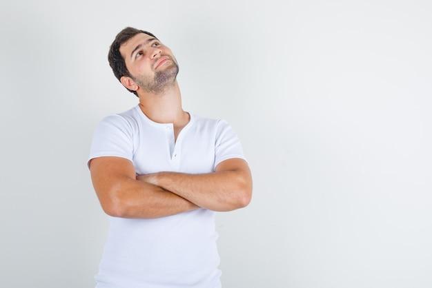 Jonge man in wit t-shirt opzoeken met gekruiste armen en hoopvol kijken