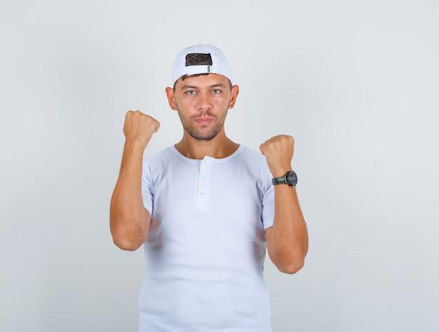 Jonge man in wit t-shirt, pet opheffen en vuisten tonen en op zoek naar sterk, vooraanzicht.