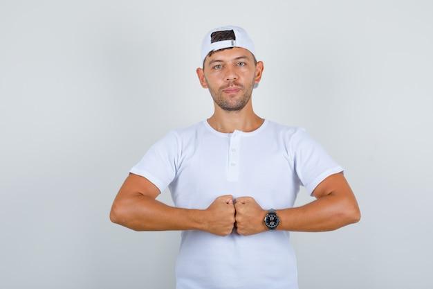 Jonge man in wit t-shirt, pet stoot zijn vuisten en kijkt zelfverzekerd, vooraanzicht.