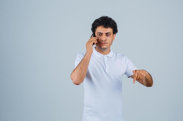 Jonge man in wit t-shirt praten op mobiele telefoon, naar beneden wijzend en nerveus, vooraanzicht.