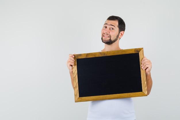 Jonge man in wit t-shirt staande met zwarte bord te houden en klaar te kijken, vooraanzicht.