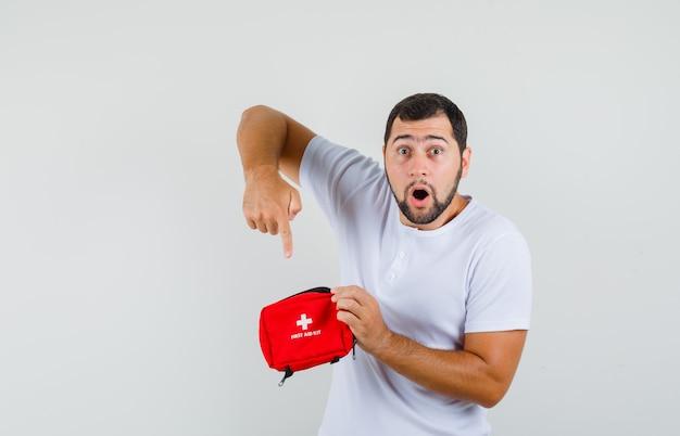 Jonge man in wit t-shirt wijzend op ehbo-doos en op zoek verrast, vooraanzicht.