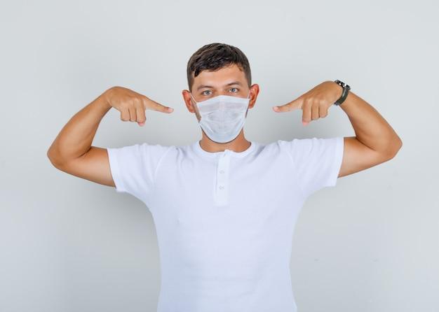Jonge man in wit t-shirt wijzende vingers op medisch masker, vooraanzicht.