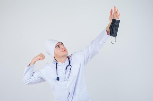 Jonge man in wit uniform maakt zich klaar om op medisch masker te kloppen en kijkt boos, vooraanzicht.