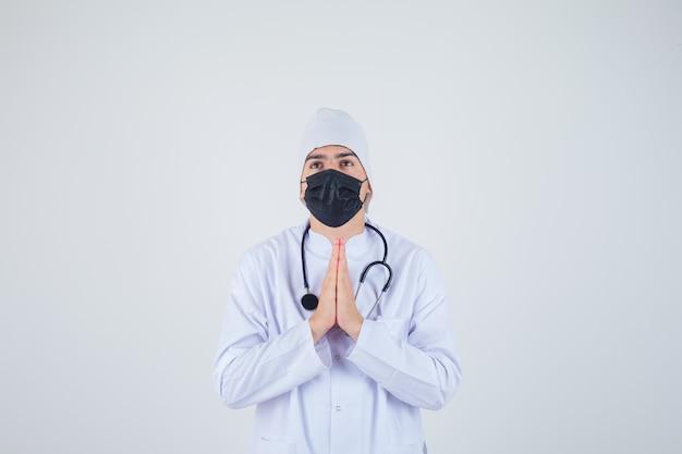 Jonge man in wit uniform, masker houden handen in biddend gebaar en op zoek hoopvol, vooraanzicht.