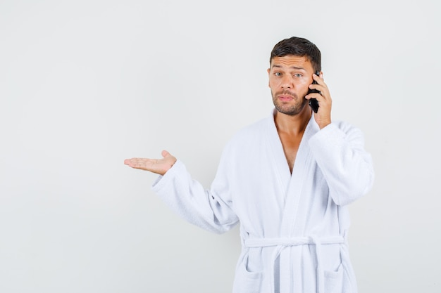 Jonge man in witte badjas praten over de telefoon met hulpeloos gebaar opzij, vooraanzicht.