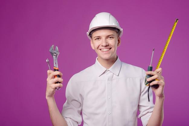 Jonge man in witte helm met werkinstrument in de hand op paarse achtergrond