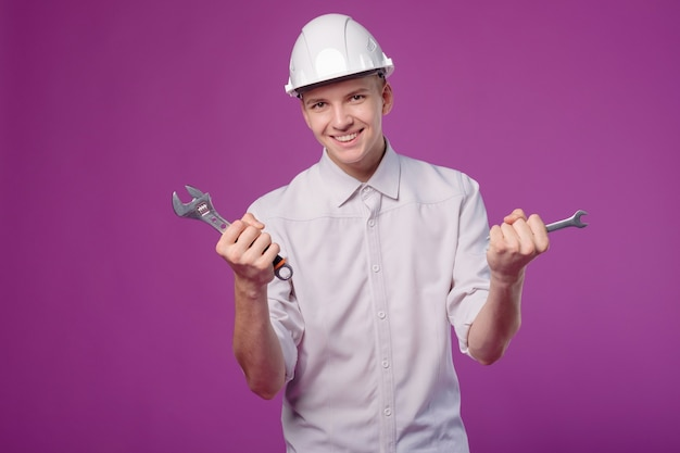 Jonge man in witte helm met werkinstrument in hand op paarse achtergrond