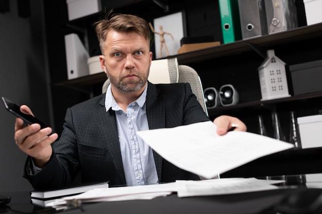 Jonge man in zakelijke kleding werkt op computer bureau met telefoon en documenten