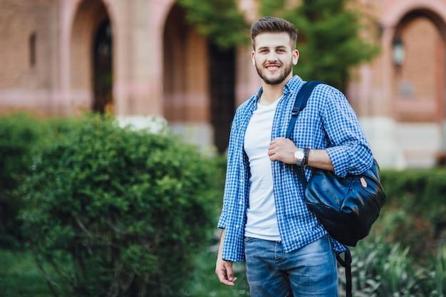 Jonge man in zonnebril en in een wit overhemd met grijze broek die op zijn telefoon spreekt met een kopje koffie