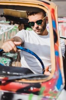 Jonge man in zonnebril in een cabriolet