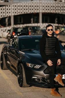 Jonge man in zonnebril in zwarte outfit vormt door zijn zwarte auto