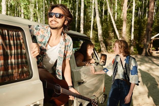 Jonge man in zonnebril met gitaar die met zijn vrienden in het bos reist