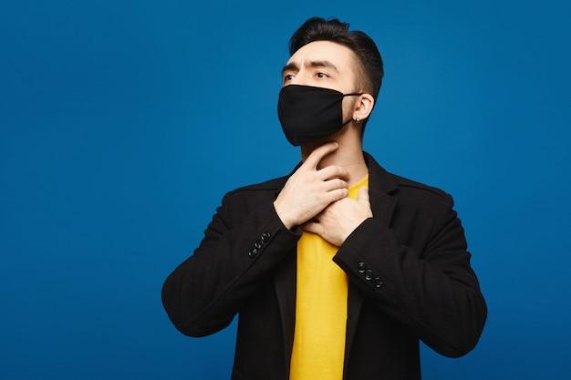 Jonge man in zwart beschermend masker met keelpijn