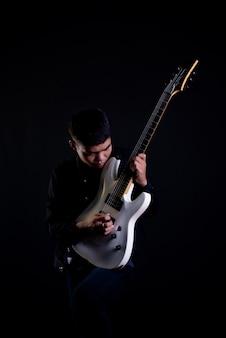 Jonge man in zwart lederen jas met elektrische gitaar