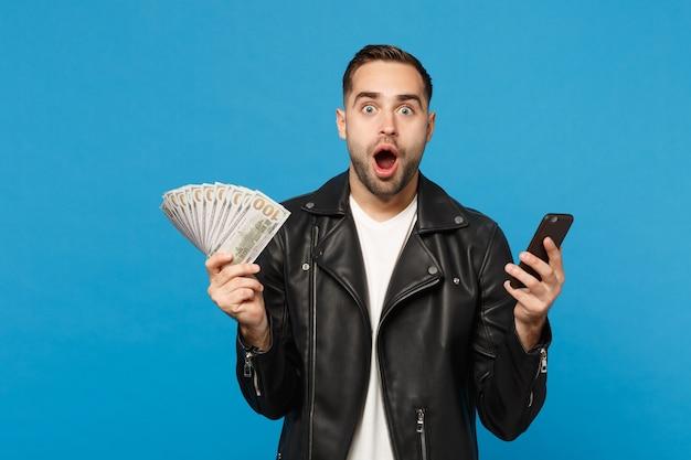 Jonge man in zwart lederen jas wit t-shirt met fan van contant geld in dollarbankbiljetten, mobiele telefoon geïsoleerd op blauwe muur achtergrond studio portret. mensen levensstijl concept. bespotten kopie ruimte.