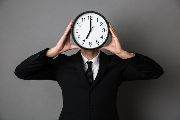 Jonge man in zwart pak bedrijf klok voor zijn gezicht