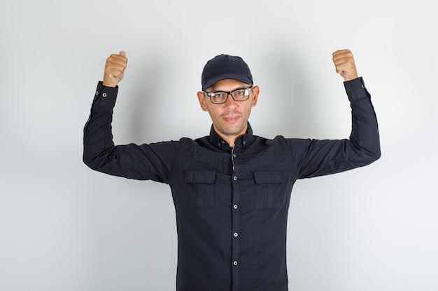 Jonge man in zwart shirt met pet, bril met vingers naar achteren en op zoek vrolijk