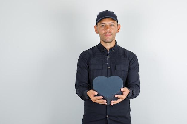 Jonge man in zwart shirt met pet geschenkdoos houden en op zoek vrolijk