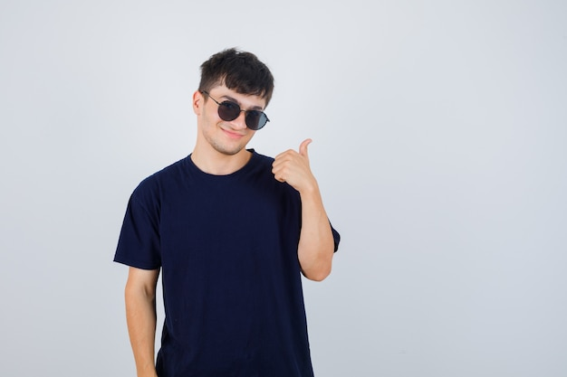 Jonge man in zwart t-shirt duim opdagen en op zoek zelfverzekerd, vooraanzicht.