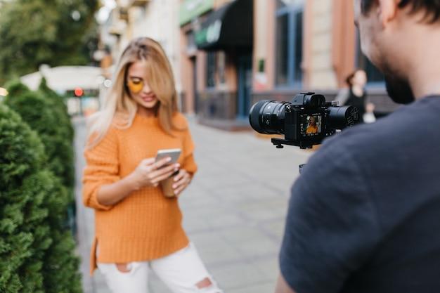 Jonge man in zwart t-shirt foto van blije blonde vrouw in oranje trui maken