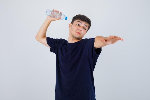 Jonge man in zwart t-shirt klaar om fles water weg te gooien en kijkt boos, vooraanzicht.