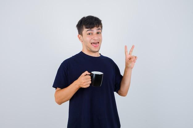 Jonge man in zwart t-shirt met kopje thee, v-teken tonen en op zoek gelukkig, vooraanzicht.