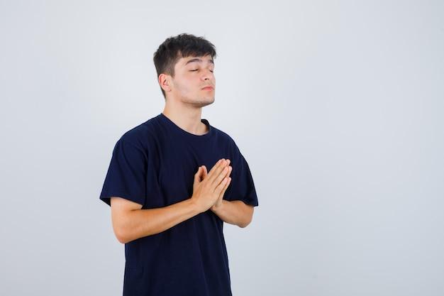 Jonge man in zwart t-shirt met namaste-gebaar en op zoek naar hoopvol, vooraanzicht.