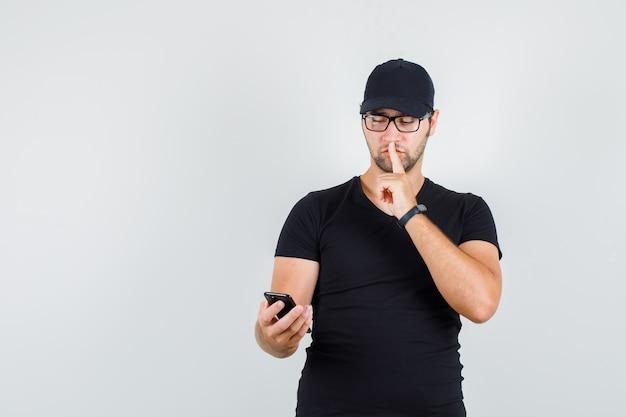Jonge man in zwart t-shirt, pet, bril smartphone met stilte gebaar kijken