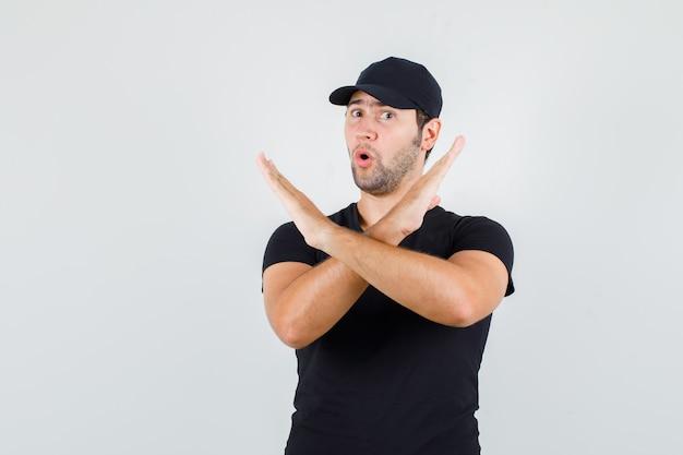 Jonge man in zwart t-shirt, pet met stopgebaar en opgewonden kijkt