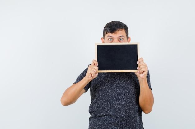 Jonge man in zwart t-shirt verbergen achterkant zwart karton en kijkt opgewonden, vooraanzicht.