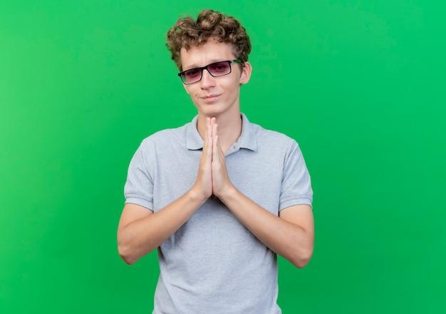 Jonge man in zwarte bril die een grijs poloshirt draagt dat de handpalmen tegen elkaar houdt als namaste-gebaar, dankbaar gevoel over groene muur te staan