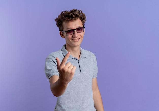 Jonge man in zwarte bril draagt een grijs poloshirt en maakt kom hier gebaar met hand die over blauwe muur staat
