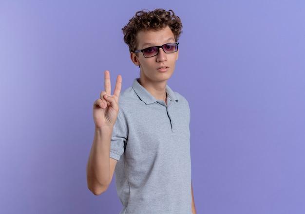 Jonge man in zwarte bril draagt grijs poloshirt met seriosu gezicht tonen en omhoog met vingers nummer twee over blauw