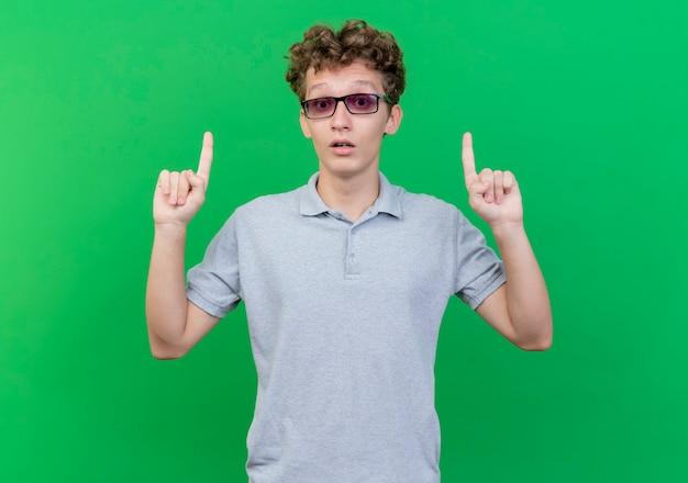 Jonge man in zwarte bril draagt grijs poloshirt wijzend met idex vingers omhoog verrast staande over groene muur