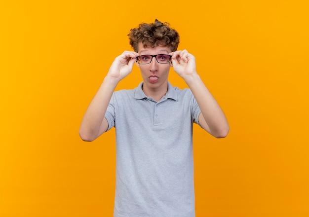 Jonge man in zwarte bril dragen grijs poloshirt maken grimas tong uitsteekt staande over oranje muur