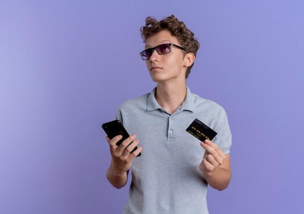Jonge man in zwarte bril dragen grijs poloshirt met smartphone en creditcard kijken verbaasd staande over blauwe muur