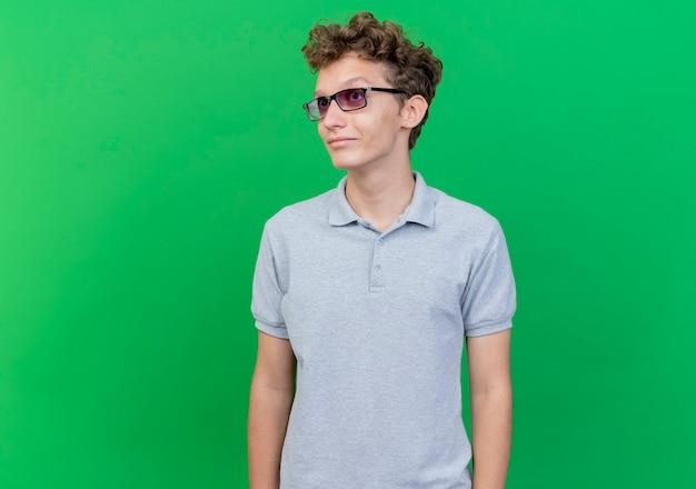 Jonge man in zwarte bril dragen grijs poloshirt opzij kijken met glimlach op gezicht staande over groene muur
