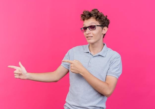 Jonge man in zwarte bril, gekleed in een grijs poloshirt, blij en positief wijzend met de vingers naar de zijkant over roze