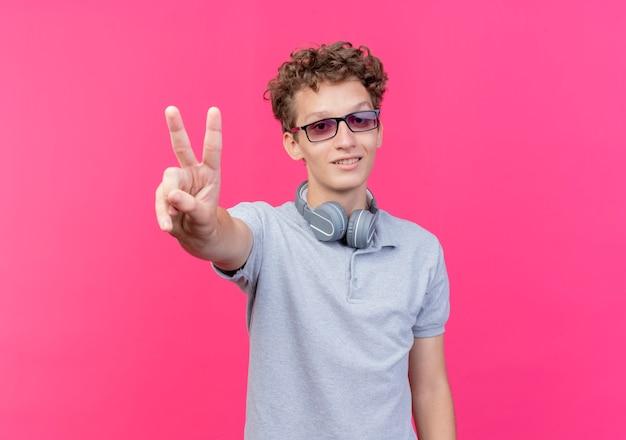 Jonge man in zwarte bril, gekleed in grijs poloshirt lachend met v-sign blij en vrolijk over roze