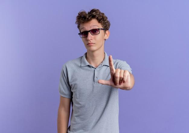 Jonge man in zwarte bril, gekleed in grijs poloshirt met ernstig gezicht wijsvinger waarschuwing staande over blauwe muur
