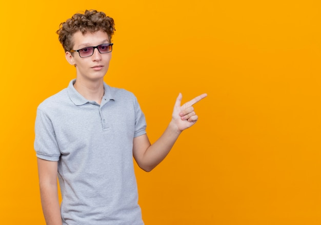 Jonge man in zwarte bril, gekleed in grijs poloshirt met ernstig gezicht wijzend met de vinger naar de zijkant over oranje