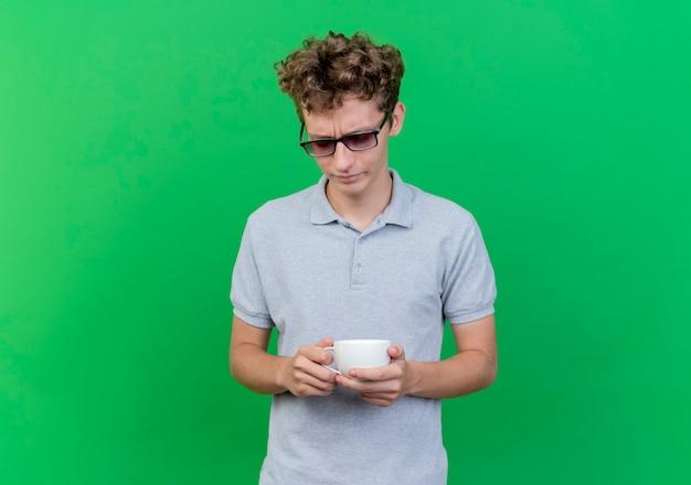 Jonge man in zwarte bril, gekleed in grijs poloshirt met koffiekopje neerkijkt met droevige uitdrukking staande over groene muur