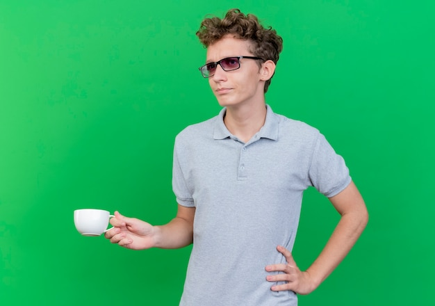Jonge man in zwarte bril, gekleed in grijs poloshirt met koffiekopje opzij kijken verward en ontevreden staande over groene muur