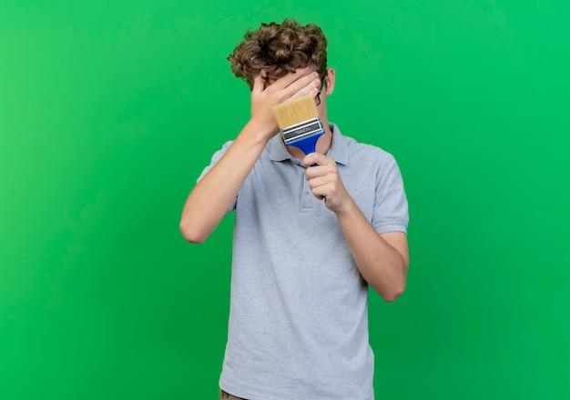Jonge man in zwarte bril, gekleed in grijs poloshirt met kwast die gezicht bedekt met een hand wordt verward staande over groene muur