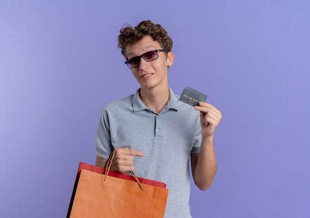 Jonge man in zwarte bril, gekleed in grijs poloshirt met papieren zakken met creditcard glimlachend staande over blauwe muur