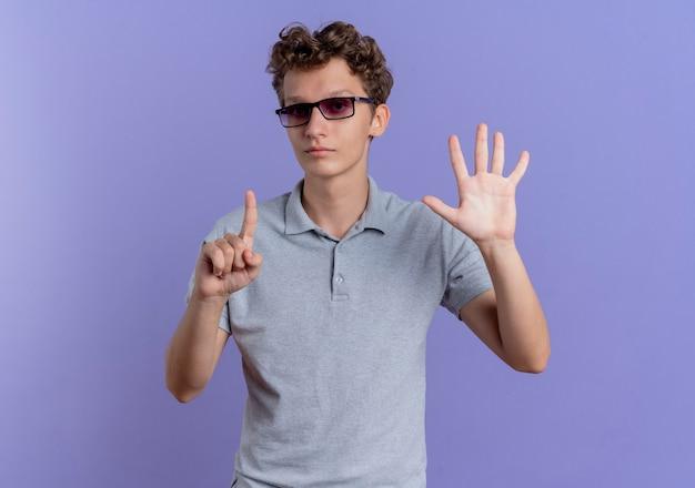 Jonge man in zwarte bril, gekleed in grijs poloshirt met seriosu gezicht tonen en omhoog met vingers nummer zes staande over blauwe muur
