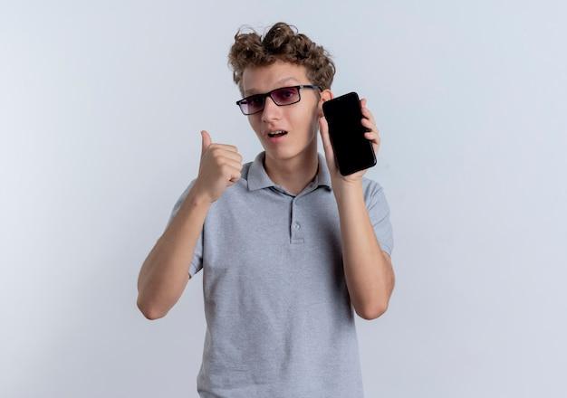 Jonge man in zwarte bril, gekleed in grijs poloshirt met smartphone die terug wijst op zoek verward staande over witte muur