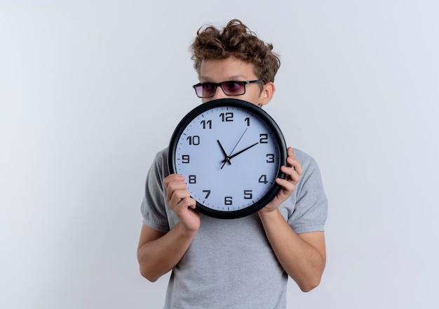 Jonge man in zwarte bril, gekleed in grijs poloshirt met wandklok die zijn gezicht erachter verbergt staande over een witte muur