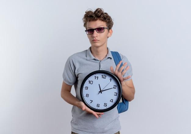 Jonge man in zwarte bril, gekleed in grijs poloshirt met wandklok met ernstig gezicht staande over witte muur